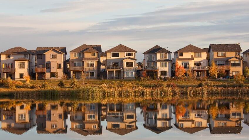 A row of houses reflected in a pond.