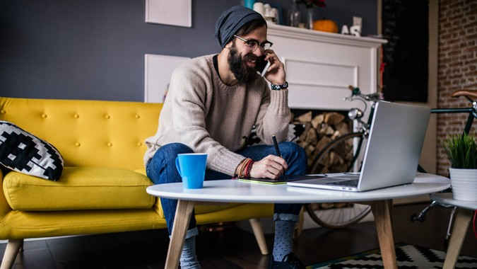 Smiling webdesigner working from his home office.