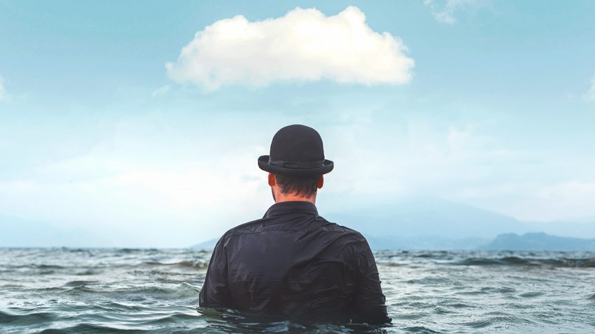 man with hat in water with cloud