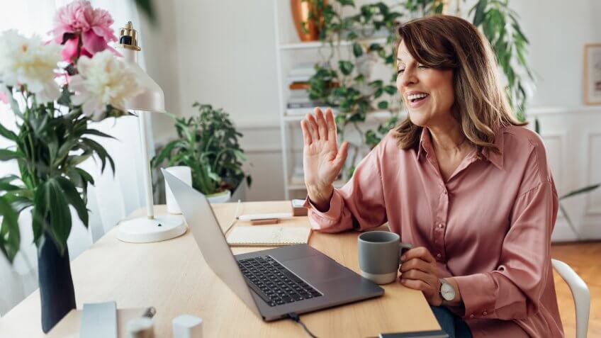 Smiling mature woman attending an online meeting from the comfort of her home office.