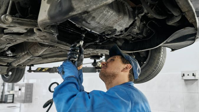 Professional mechanic man in blue uniform working with tools under lifted car in repair service.