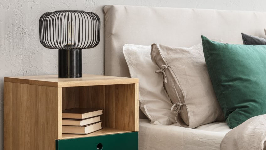 Beige and emerald bedroom design with modern lamp on wooden nightstand table.