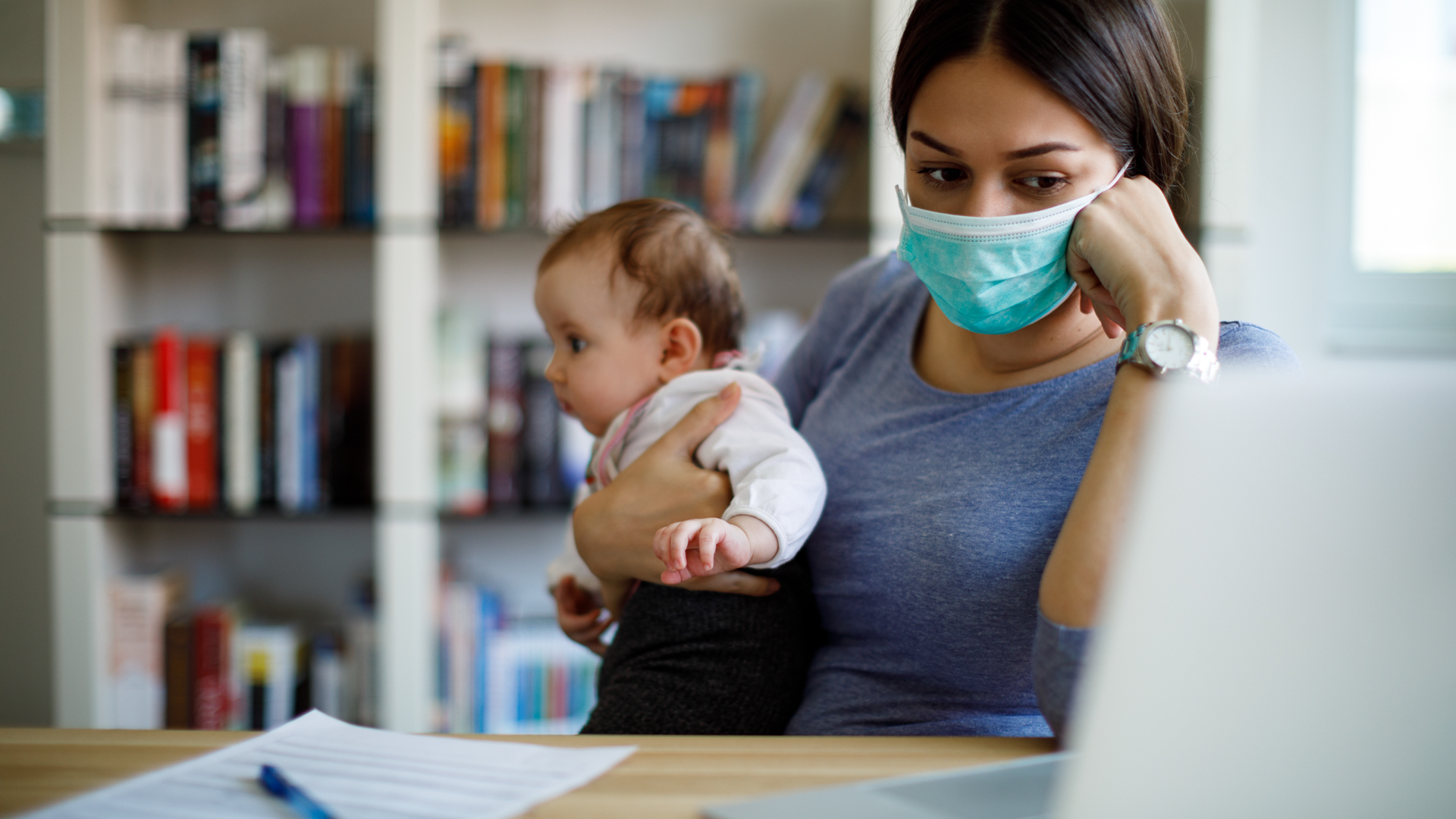 Worried mother with face protective mask working from home.