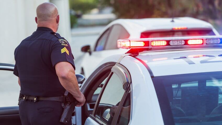 Policeman pulls over a driver for speeding, getting out of police car to write a traffic ticket.