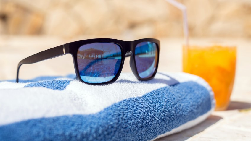 Sunglasses on a towel reflecting blue pool with a drink on the side.