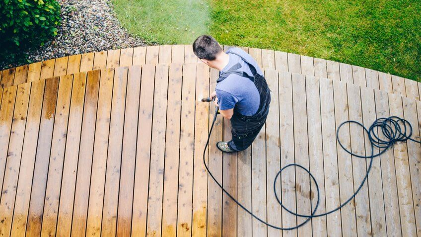 cleaning terrace with a power washer - high water pressure cleaner on wooden terrace surface.