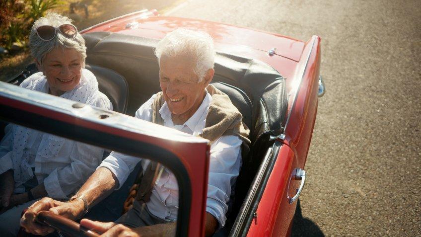 senior couple driving luxury new car in retirement