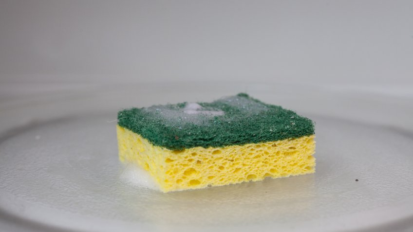 A green and yellow sponge covered in soap suds sits inside of a microwave.