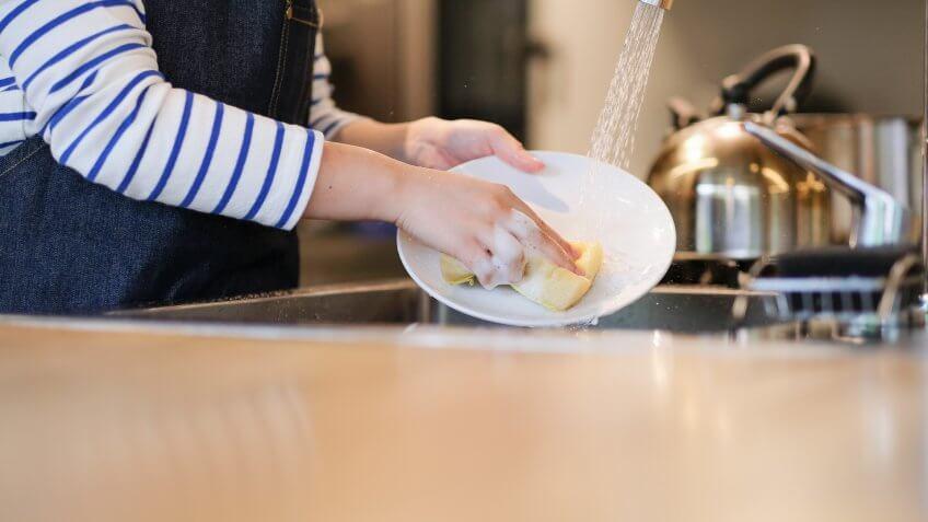 Waitress washing dish in the kitchen of restaurant.