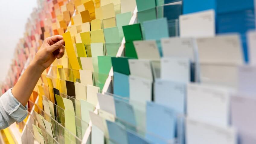 Close-up on a customer holding a color sample at a home improvement store - remodeling and painting concepts.