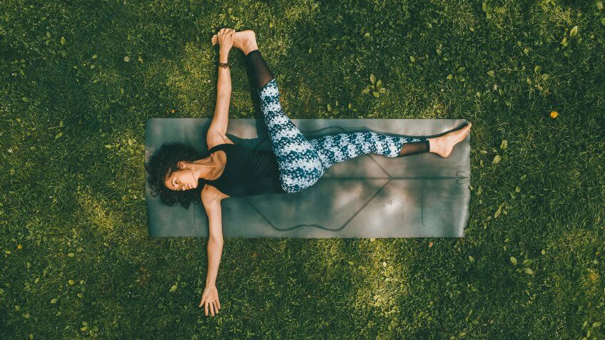 woman doing yoga stretch on park grass