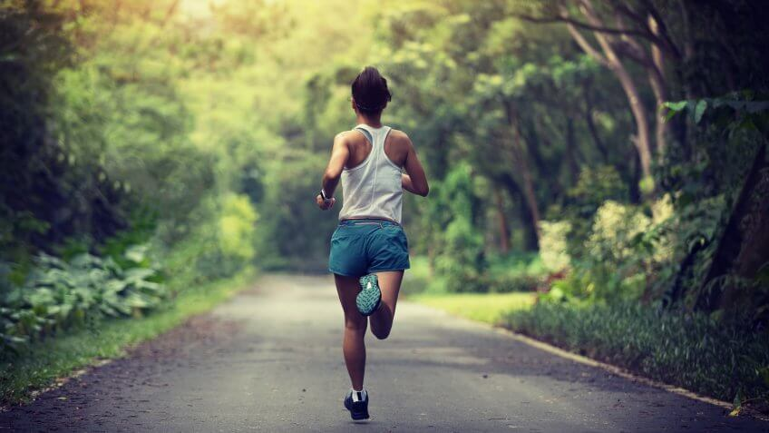Female runner running at summer park trail .