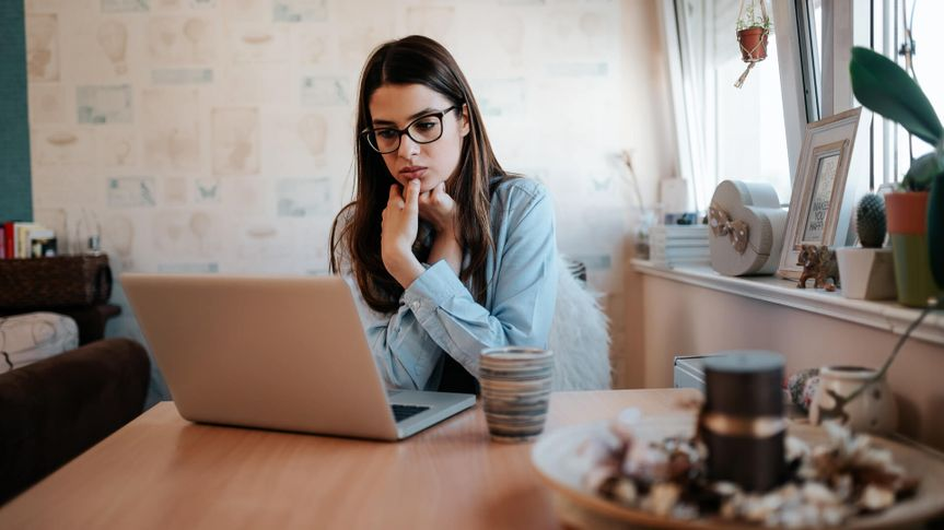 Worried girl looking at laptop screen at home.
