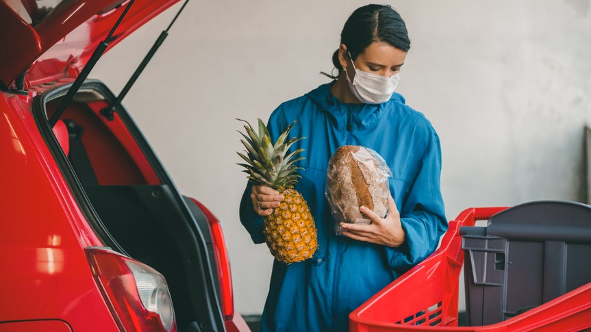 Young woman wears medical face mask against corona virus covid-19 in parking garage.