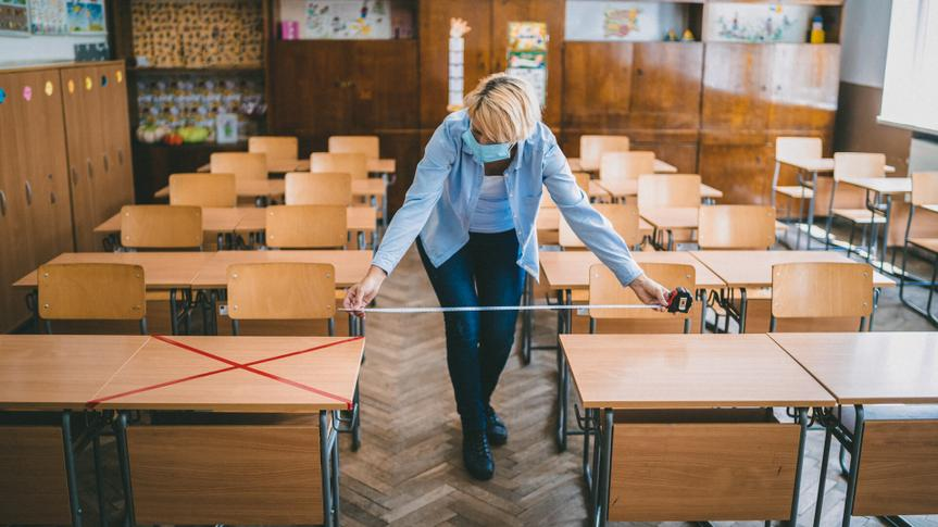 Teacher measuring and marking places in the classroom for returning of students after the coronavirus pandemic.