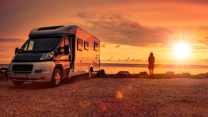 Woman at sunset  with mobile home on the beach.