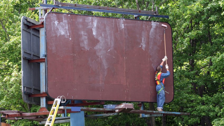 Media sign worker prepares billboard with adhesive prior to installing new advertisement.