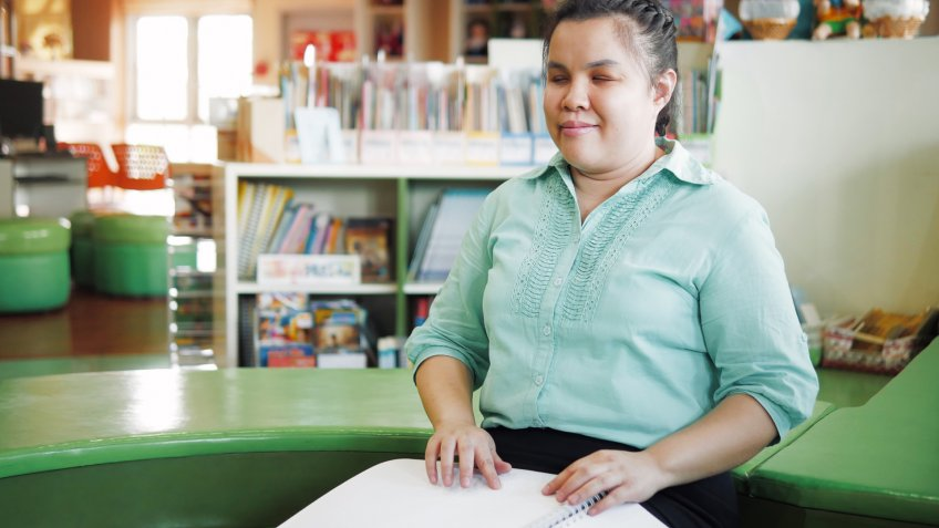 Portrait of Asian young blind woman disabled person reading Braille book in creative workplace.
