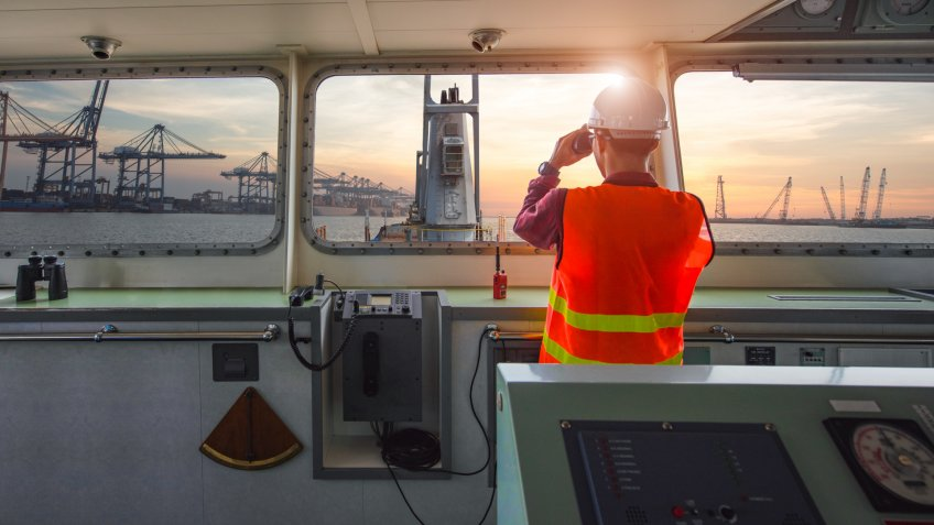 pilot, port control or duty officer in charge handle of the ship navigating to the port destination, keep watching navigation on the bridge of the ship vessel under voyage sailing to the sea.
