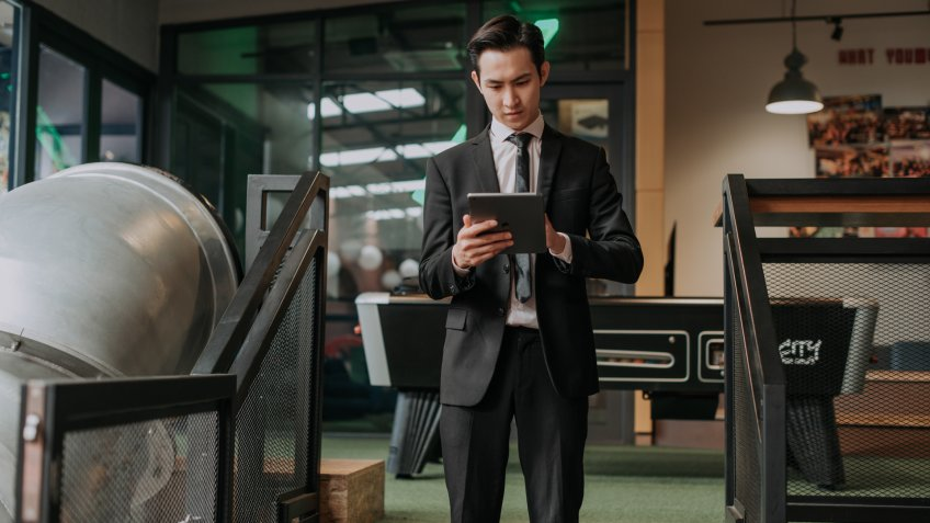 an asian chinese male young executive using digital tablet surfing the net in a cafe.