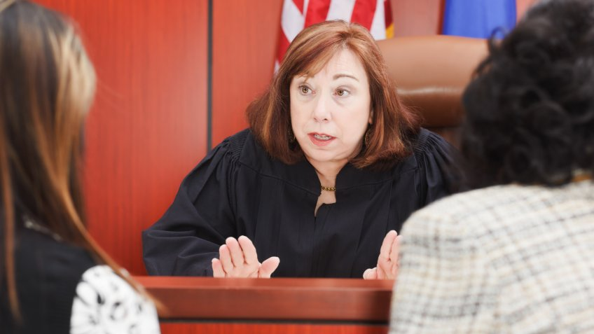 Two female lawyers speaking to a Judge in the courtroom.