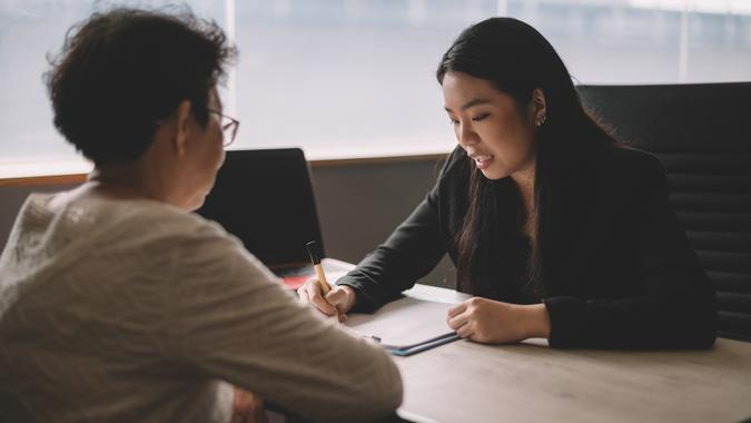 an asian chinese active senior woman having discussion with her chinese agent about her retirement investment plan.