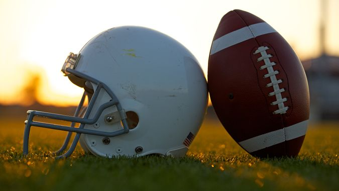American Football and Helmet on the Field Backlit at Sunset.
