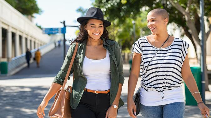 Young smiling women walking and talking while looking at each other outdoor.