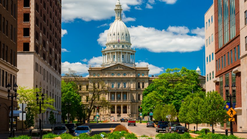 Lansing, United States - May 24, 2014 - The Michigan State Capitol as viewed from within Downtown Lansing, with trees, plants, office buildings, and pedestrians and cars and a driver in the foreground, and a blue sky with clouds in the background.