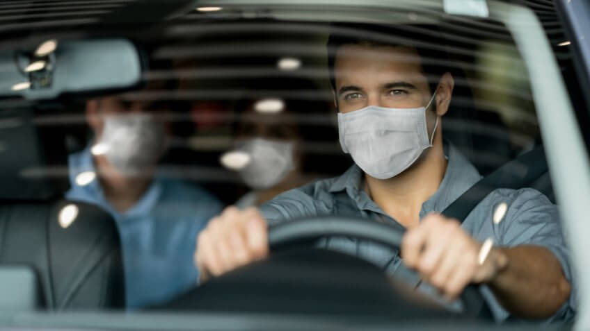 Portrait of a crowdsource taxi driver wearing a facemask while driving a couple of customers during the COVID-19 pandemic.