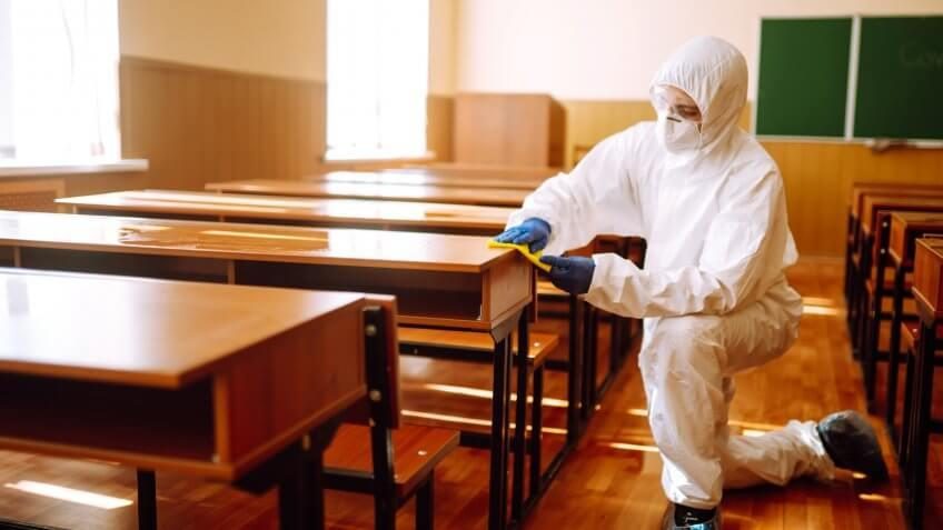 Man in a protective suit washes school desk.