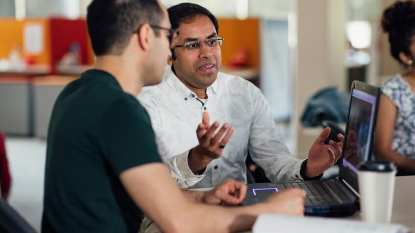 Two men can be seen mid-discussion during a scientific seminar.