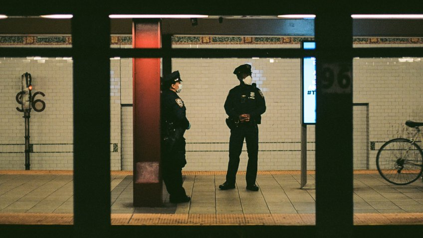Two NYPD officers wear N95 face masks on the 96th street station subway platform in the Upper West Side.