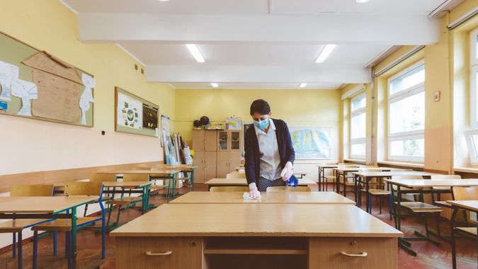 The teacher wipes down tables in the classroom before students return to school after the coronovirus pandemic.