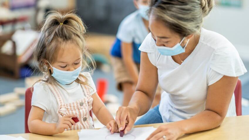 Cute young girl colouring in a daycare facility while wearing a protective face mask to avoid the transfer of germs during COVID-19.