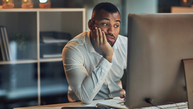 Shot of a young businessman looking bored while working at his desk during late night at work.