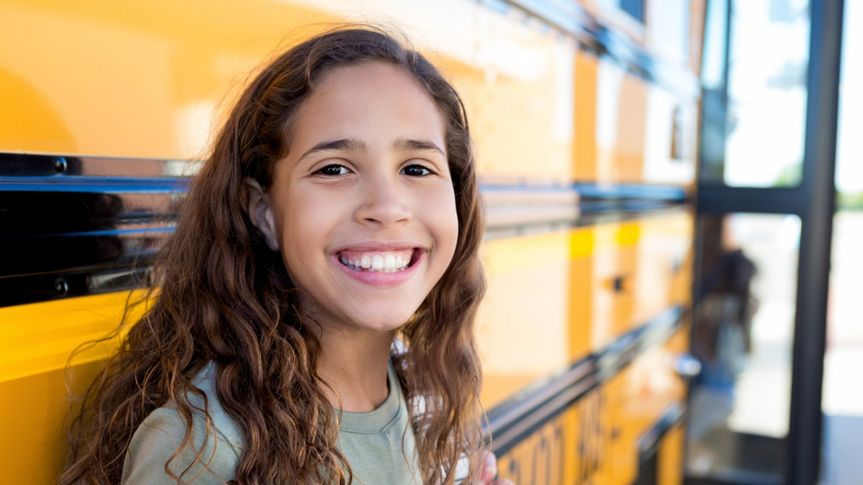 Female middle schoolgirl smiles at the camera while waiting to board school bus.