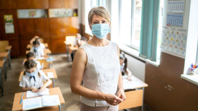 Young elementary teacher wearing a protective face mask at school.