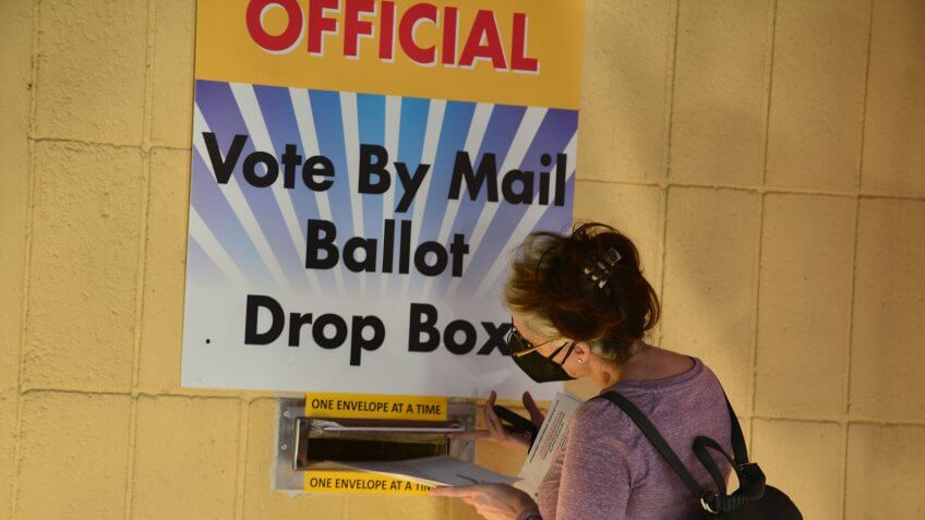 Mandatory Credit: Photo by JLN Photography/Shutterstock (10748887p)Voter drop their ballot at the drop box at Broward County Supervisor of Election Headquarters in Lauderhill, Florida, U.