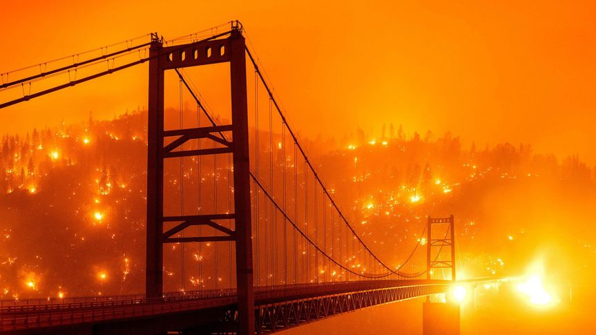 Mandatory Credit: Photo by Noah Berger/AP/Shutterstock (10770872f)In this image taken with a slow shutter speed, embers light up a hillside behind the Bidwell Bar Bridge as the Bear Fire burns in Oroville, Calif.