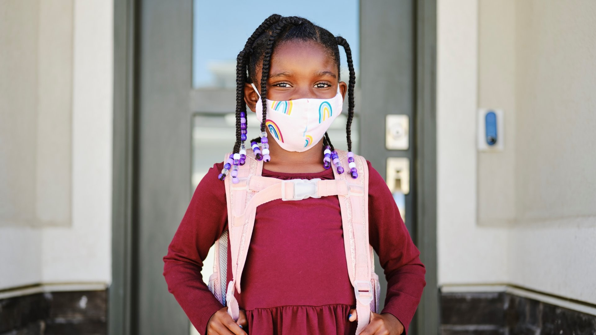 An elementary aged school student leaving her home to go back to school, wearing a mask for protection against infectious disease.