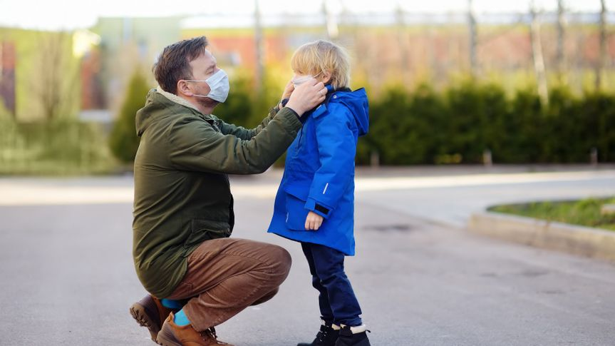 Mature man wearing a protective mask puts a face mask on a his son in airport, supermarket or other public place.