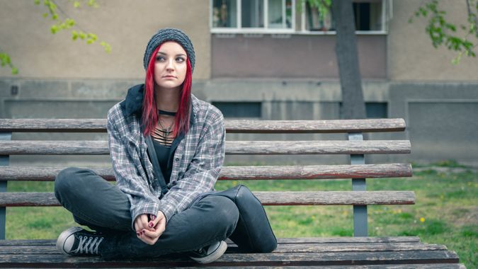 Young beautiful red hair girl sitting alone outdoors on the wooden bench on the street with hat and shirt feeling anxious and depressed after she became a homeless person.