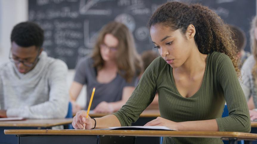 A mixed race teenage girl is taking a high school standardized test in class.