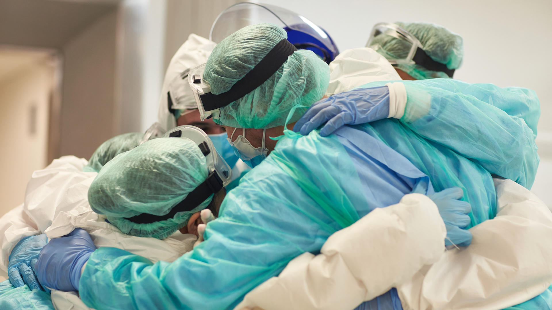 Partial view of hard-working male and female hospital team in full protective wear standing together in group embrace.