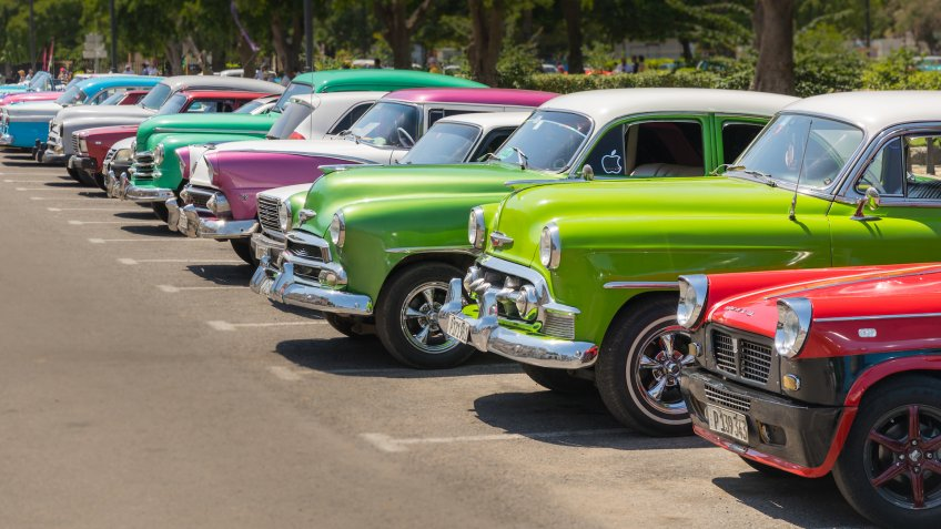 Havana, Cuba - July 23, 2018; A row of typical colorful Cuban oldtimer classic cars standing in line during day time on a parking lot.
