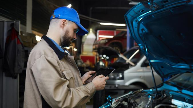 Cuacsian man with beard on face working in auto service workshop using tablet PC, horizontal side view shot.