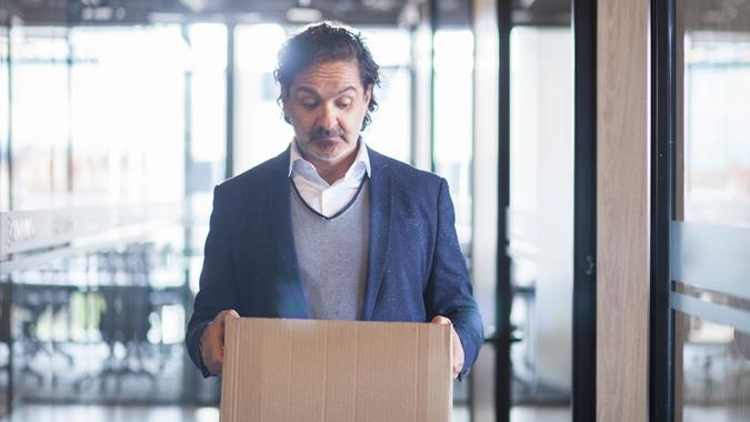 Latin executive man of approximately 50 years dressed in blue suit gray coat and white shirt walks through the corridors of the company where he works with a cardboard box where he carries his personal things in his hands which looks sadly since it was fired from his work half body picture.