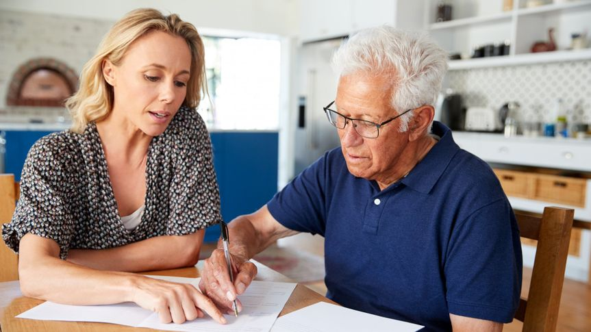 Woman Helping Senior Man To Complete Last Will And Testament At Home.