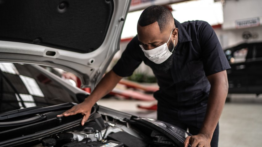 Auto mechanic man with face mask working at auto repair shop.